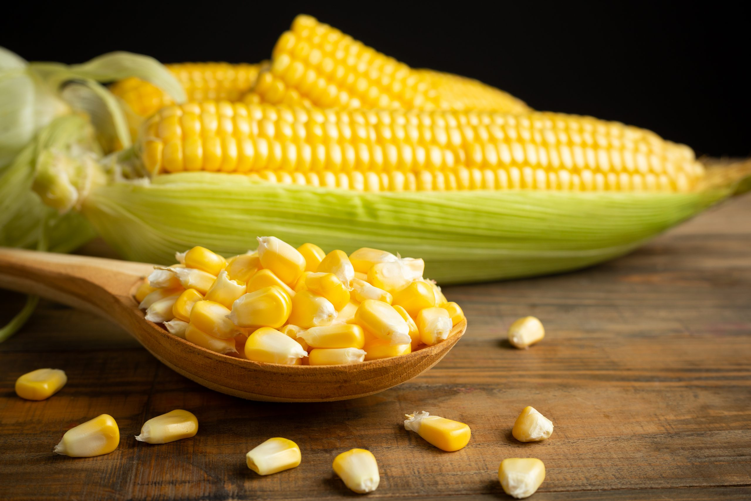seeds and sweet corn on wooden table.